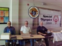 "At ""A Knight's Break"" brunch fundraiser at St. Patrick's High School Brothers Angelo and Jerry help District Deputy Brian obtain signatures on the Special Olympics flag."